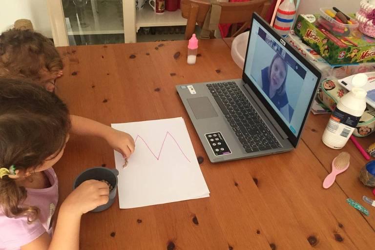 Crianças assistem aula diante de computador