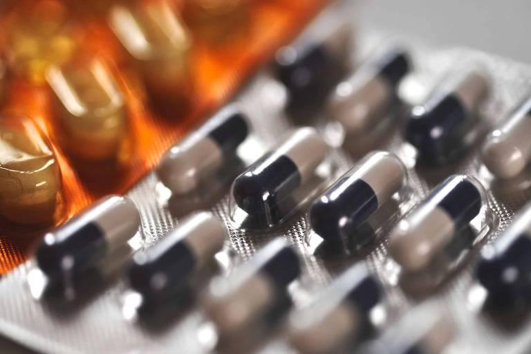 Cartela de remédio com comprimidos branco e preto