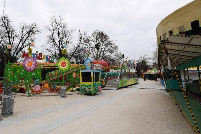 Brinquedos de parque de diversão com árvores desfolhadas ao fundo
