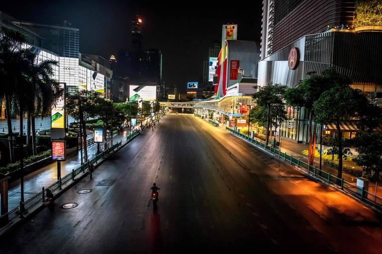 Homem de moto em avenida vazia em Bancoc, em meio à pandemia de coronavírus