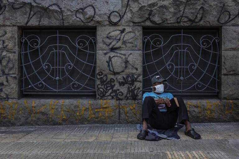 O morador de rua Marinaldo Santana, 38, aguarda comida lendo a Bíblia na calçada; ele diz que passou dias só bebendo água