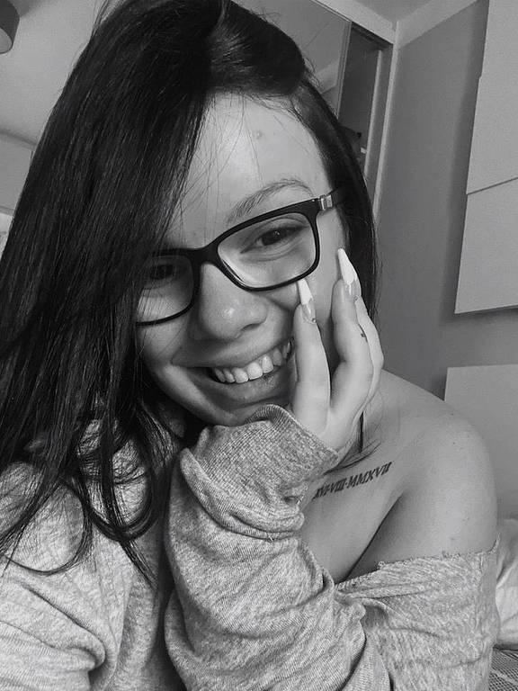 meninda de óculos sorri para a foto em preto e branco
