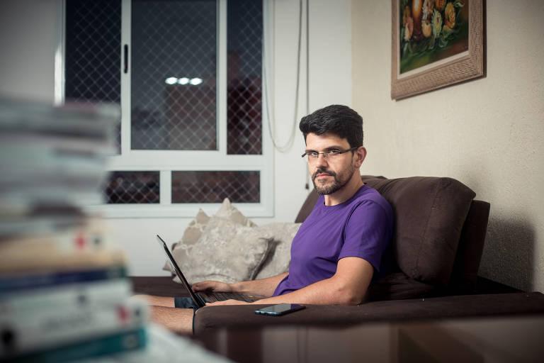 Douglas sentado no sofá com um computador no colo e o celular no braço do sofá