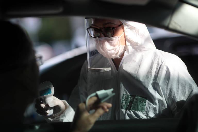 Enfermeira com trajes de prevenção (máscara, luvas, viseira transparente) mede temperatura de homem dentro de um carro