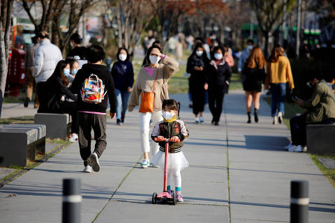 A girl wearing a protective face mask to prevent contracting the coronavirus disease (COVID-19) rides a toy kick scooter at a park in Seoul, South Korea, April 3, 2020.    REUTERS/Heo Ran ORG XMIT: FW1