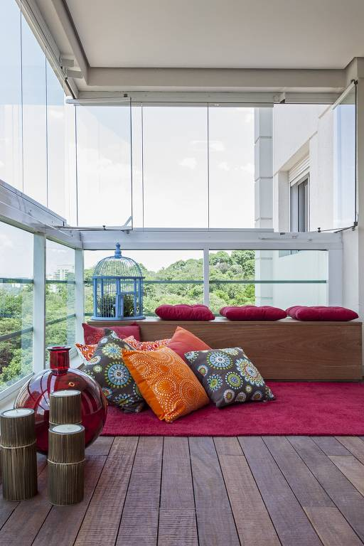 Varanda fechada com vidro, com baú de madeira, tapete e almofadas pink sobre o banco, e almofadas coloridas estampadas sobre o tapete