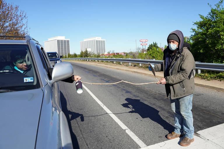 Desempregado (foto) pede esmolas com galho em Falls Church, Virgínia, nos EUA