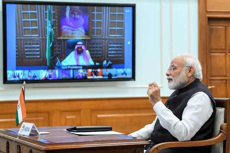 Primeiro-ministro indiano, que tem cabelo e barba brancos, está sendo em frente à tela conversando com líderes