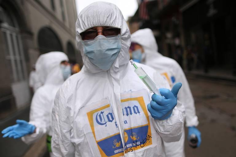 """Folião fantasiado de """"Corona"""", com máscara e roupa especial, curte o Carnaval de Nova Orleans"""