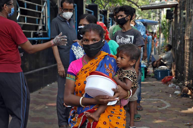 Mulher sem-teto segura filho enquanto espera para receber comida durante a quarentena em Calcutá, Índia