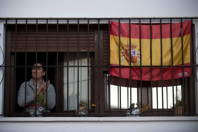 Mulher aplaude profissionais da saúde da janela de sua casa na Espanha, país mais afetado da Europa