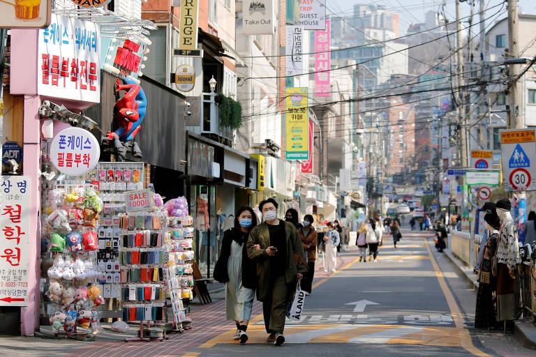 Casal veste máscaras enquanto caminham pela rua em Seul, na Coreia do Sul