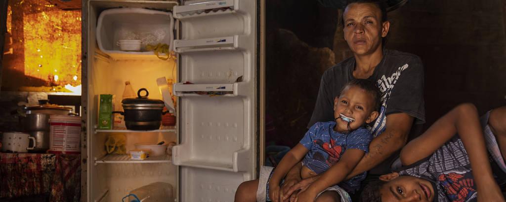 Mulher com duas crianças pequenas, sentada em cama, ao lado de geladeira aberta e vazia