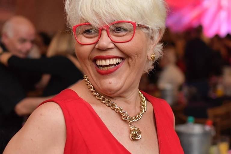 Sandra Abreu, 63, está com saudades de fazer as unhas e dançar; ela frequentava bailes de terça a domingo, antes do coronavírus; na foto vemos uma mulher sorridente, com cabelos curtos platinados, de óculos e vestido vermelhos; ao fundo, um baile