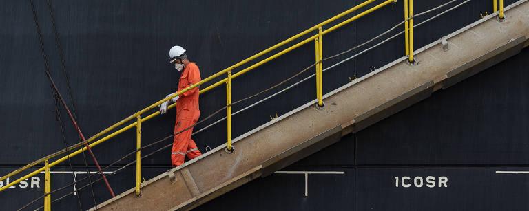 Trabalhador veste macacão amarelo; ele desce as escadas pela lateral de um navio no porto de santos