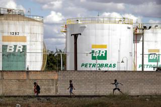 FILE PHOTO: People past in front of the tanks of Brazil's state-run Petrobras oil company in Brasilia