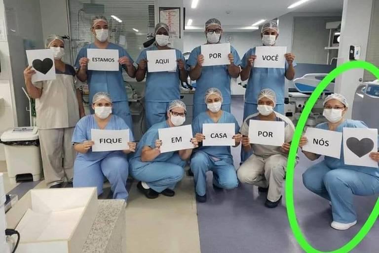Pessoas com roupas hospitalares, com máscaras, segurando cartazes