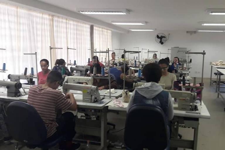 Sala com pessoas usando máquinas de costura