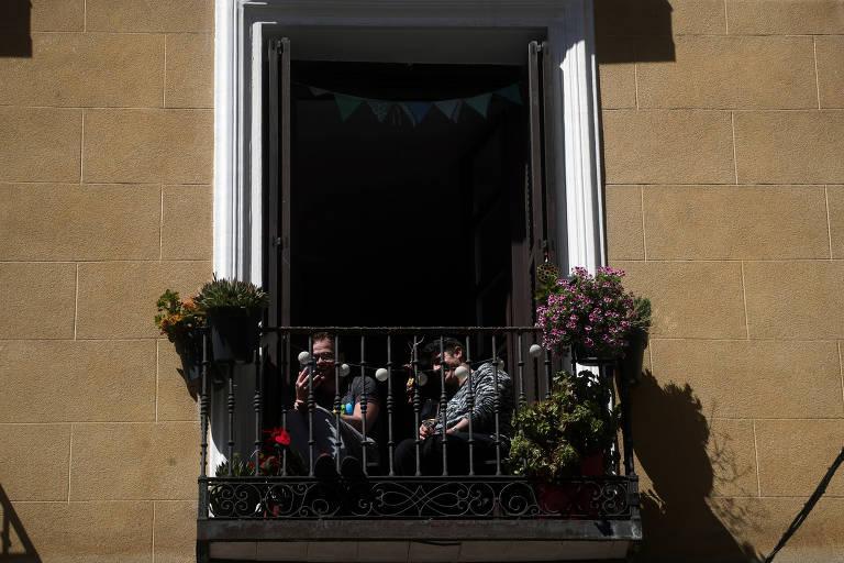 Espanhóis tomam sol na varanda durante quarentena em Madri