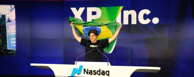 O fundador da XP, Guilherme Benchimol, posa atrás da bancada da Nasdaq segurando uma bandeira do Brasil no alto. Atrás, o logo da XP Inc. aparece escrito em um fundo azul escuro