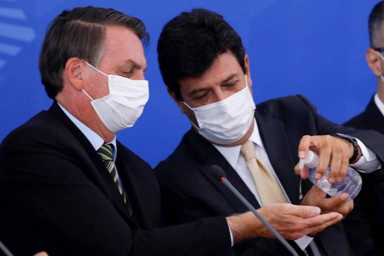 Mandetta joga álcool em gel na mão de Bolsonaro durante entrevista coletiva