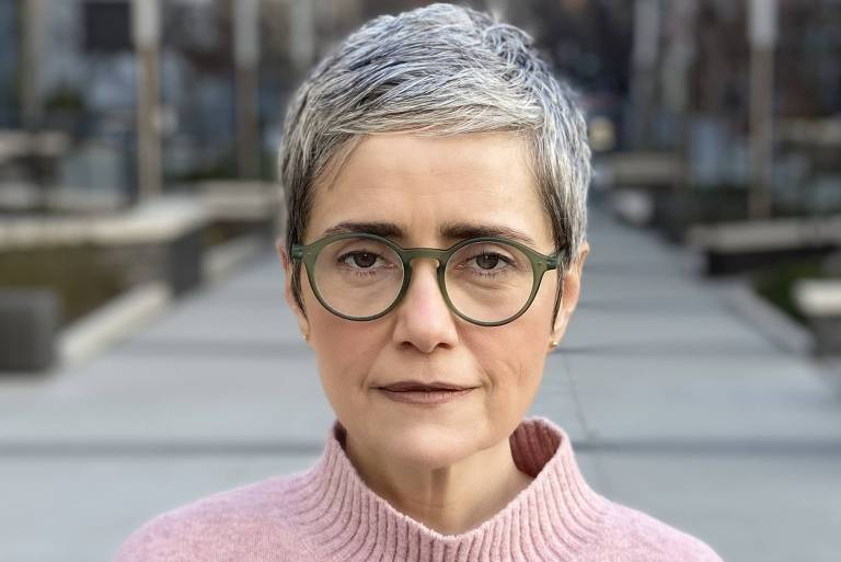 Debora Diniz olha para a câmera com expressão séria, óculos redondos e blusa rosa