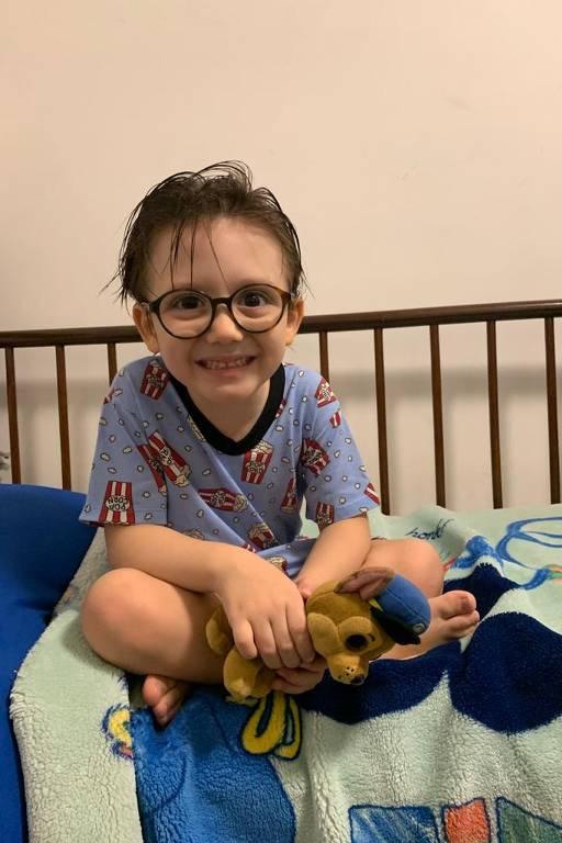 Bernardo está de pijama e óculos sentado de pernas cruzadas na cama e sorrindo