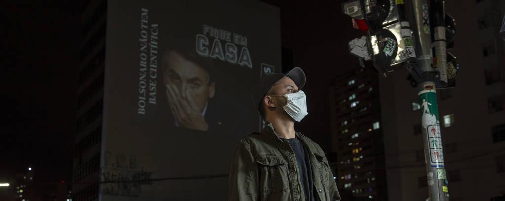 O VJ Spencer, com máscara, de pé em rua no centro de São Paulo; ao fundo, projeção em um prédio com as frases