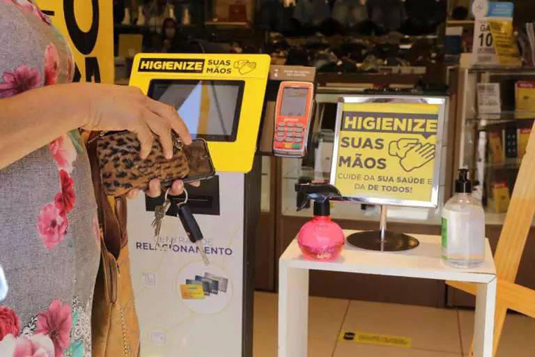 """Movimento foi intenso no primeiro dia da retomada do comércio em Campo Grande; na foto, vemos consumidora mexer na carteira em frente a cartaz junto a frascos de álcool em gel dizendo """"Higienize suas mãos"""""""