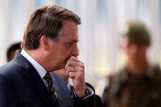 Brazil's President Jair Bolsonaro gestures near a Brazilian Army soldier as he leaves the Alvorada Palace, amid the coronavirus disease (COVID-19) outbreak