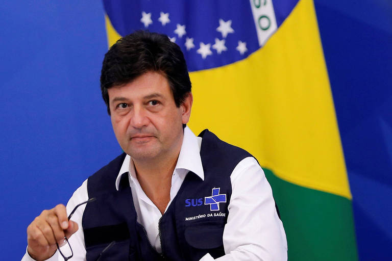 Luiz Henrique Mandetta em entrevista diária que concede sobre o avanço do coronavírus ; bandeira do Brasil ao fundo