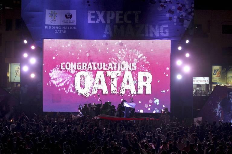 Pessoas celebram diante de telão em Doha após Qatar ser confirmado como sede da Copa de 2022