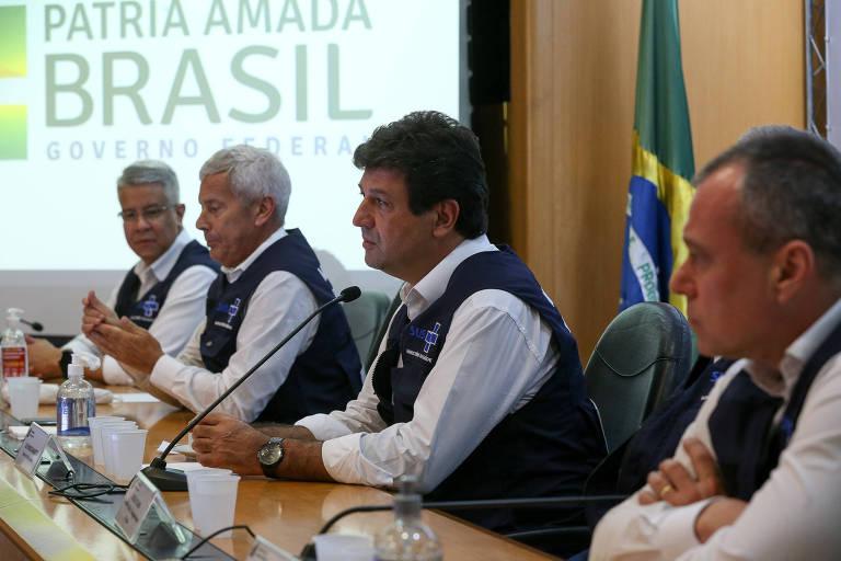 Da esquerda para a direita, Wanderson Oliveira, João Gabbardo dos Reis, Mandetta e Erno Harzheim; estão todos reunidos ao longo de uma mesa, num palco de auditório; todos usam camisa branca e o colete do SUS; ao fundo, numa tela, o slogan PÁTRIA AMADA BRASIL e uma bandeira nacional logo atrás do ministro