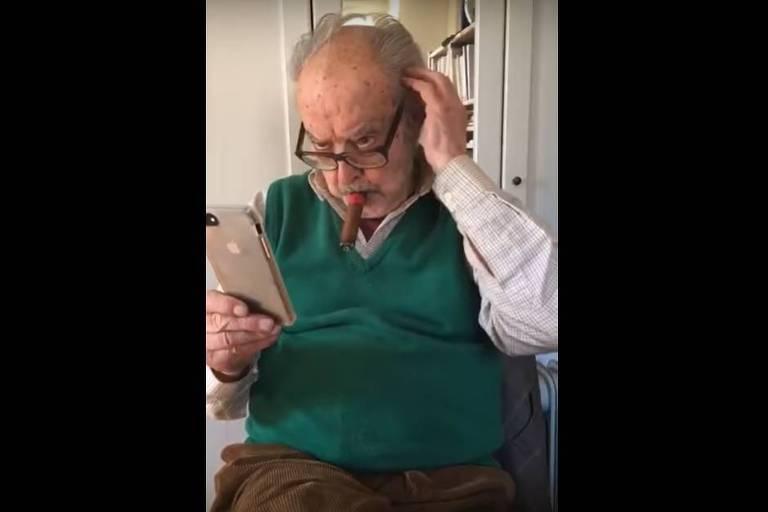 godard se penteia com celular na mão