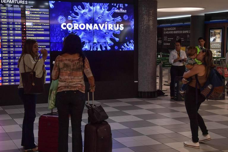 """Pessoas com mala de carrinho olhando para tela com a palavra """"coronavírus"""""""