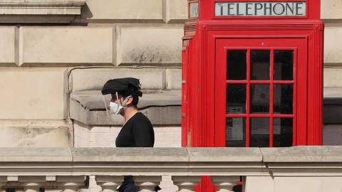 (200408) -- LONDON, April 8, 2020 (Xinhua) -- A person wearing a face mask walks past a telephone box in Parliament Square, in London, Britain on April 7, 2020. As of Tuesday morning, the number of confirmed cases in Britain hit 55,242, up 3,634 in the past 24 hours. With 726 deaths, the death toll of those hospitalized in the country reached 6,159 as of Monday afternoon, according to the Department of Health and Social Care. (Photo by Tim Ireland/Xinhua)