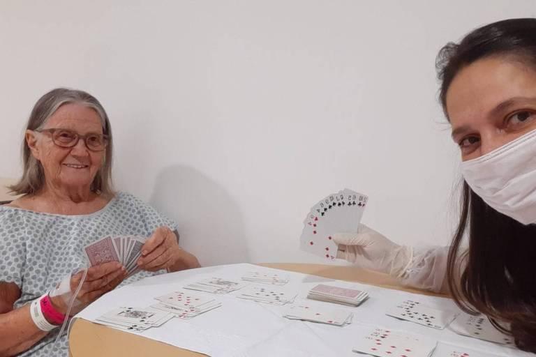 Yolanda, matriarca da família, durante internação, jogando cartas com sua neta Tatiana, que se contaminou, mas não teve sintomas; vemos uma senhora com avental de hospital, com acesso para medicamentos no braço, sentada a uma mesa com uma mulher de cabelos escuros, usando máscara e luvas