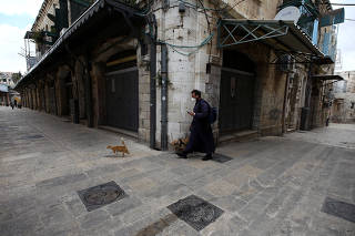 A man walks with his dog amid coronavirus restrictions in a street in Jerusalem's Old City