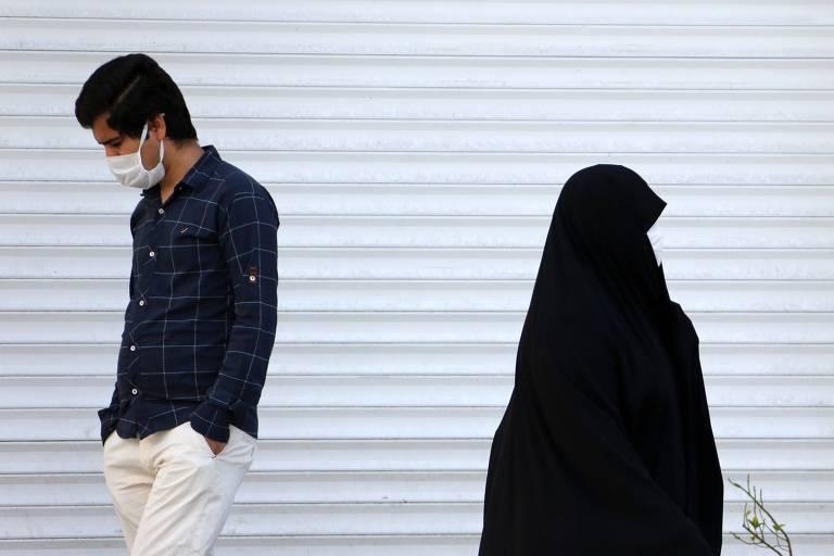 Iranianos com máscaras para tentar evitar a contaminação por coronavírus caminham em rua de Teerã