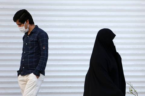 An Iranian man and a woman wearing a protective face masks against the novel coronavirus, walk past a closed shop in the capital Tehran on April 5, 2020. - The spread of the virus in Iran has slowed for the fifth day in a row, according to official figures released today by the authorities, who also announced plans for a gradual resumption of certain economic activities starting on April 11. (Photo by ATTA KENARE / AFP) ORG XMIT: AK1162