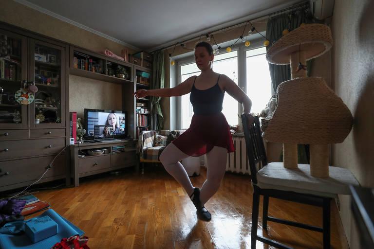 Anastasia Osipova pratica balé em seu apartamento durante uma aula por meio de um link de vídeo, depois que as autoridades da cidade anunciaram um bloqueio parcial ordenando que os moradores ficassem em casa para impedir a propagação da doença por coronavírus (COVID-19), com um gato visto nas proximidades, em Moscou, Rússia
