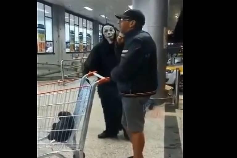 Homem vestido de Morte tenta conscientizar pessoas no mercado
