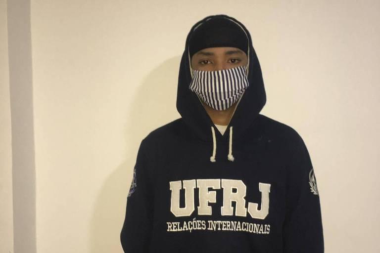 Estudante usa máscara caseira e moletom da UFRJ com capuz
