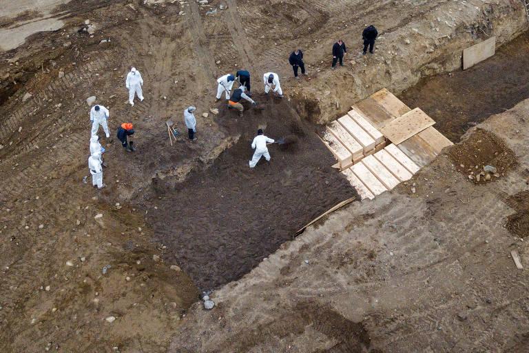 Coveiros enterram corpos em vala comum aberta em Hart Island, na cidade de Nova York