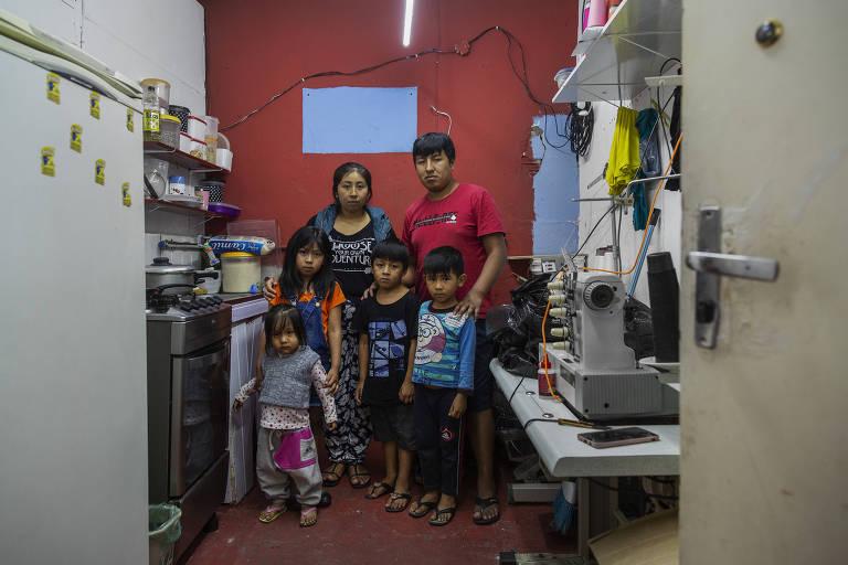 Marlene Apaza, 24, com sua família em cozinha que também funciona como oficina no Bom Retiro