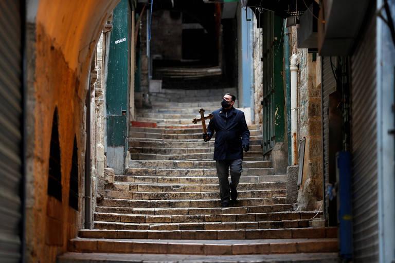 Homem sozinho carrega cruz enquanto percorre a Via Dolorosa em Jerusalém