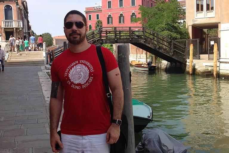 Alexey Dodsworth está de camisa vermelha e bermuda à margem de um canal de veneza