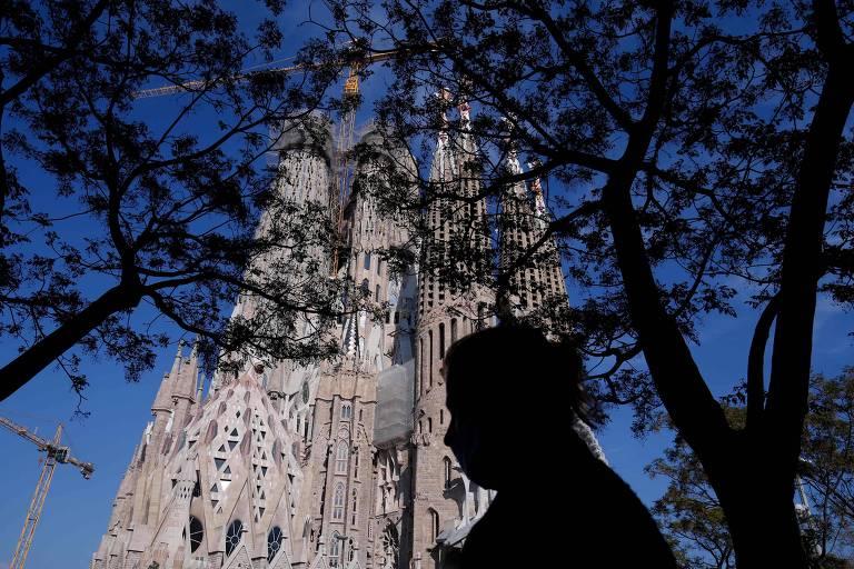 A Sagrada Família é vista de baixo. com um céu azul. A sombra de uma mulher aparece em frente a igreja