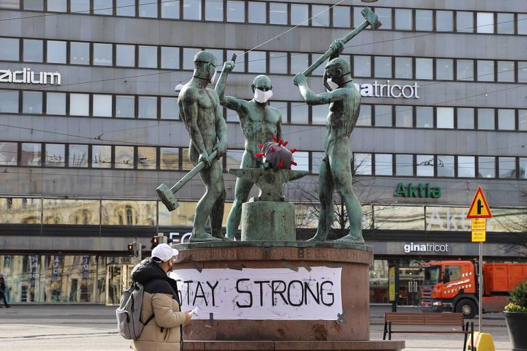 Escultura em Helsinque, capital da Finlândia, alvo de intervenção; faixa diz 'mantenha-se forte'