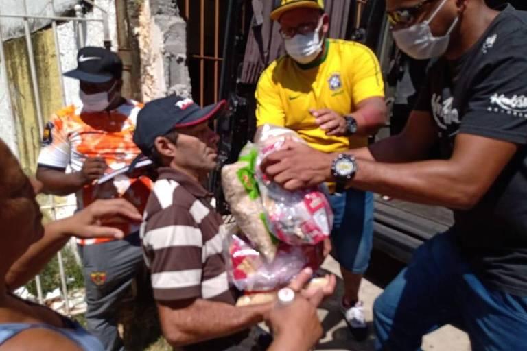 Moradores de comunidades carentes recebem alimentos da equipe de KondZilla